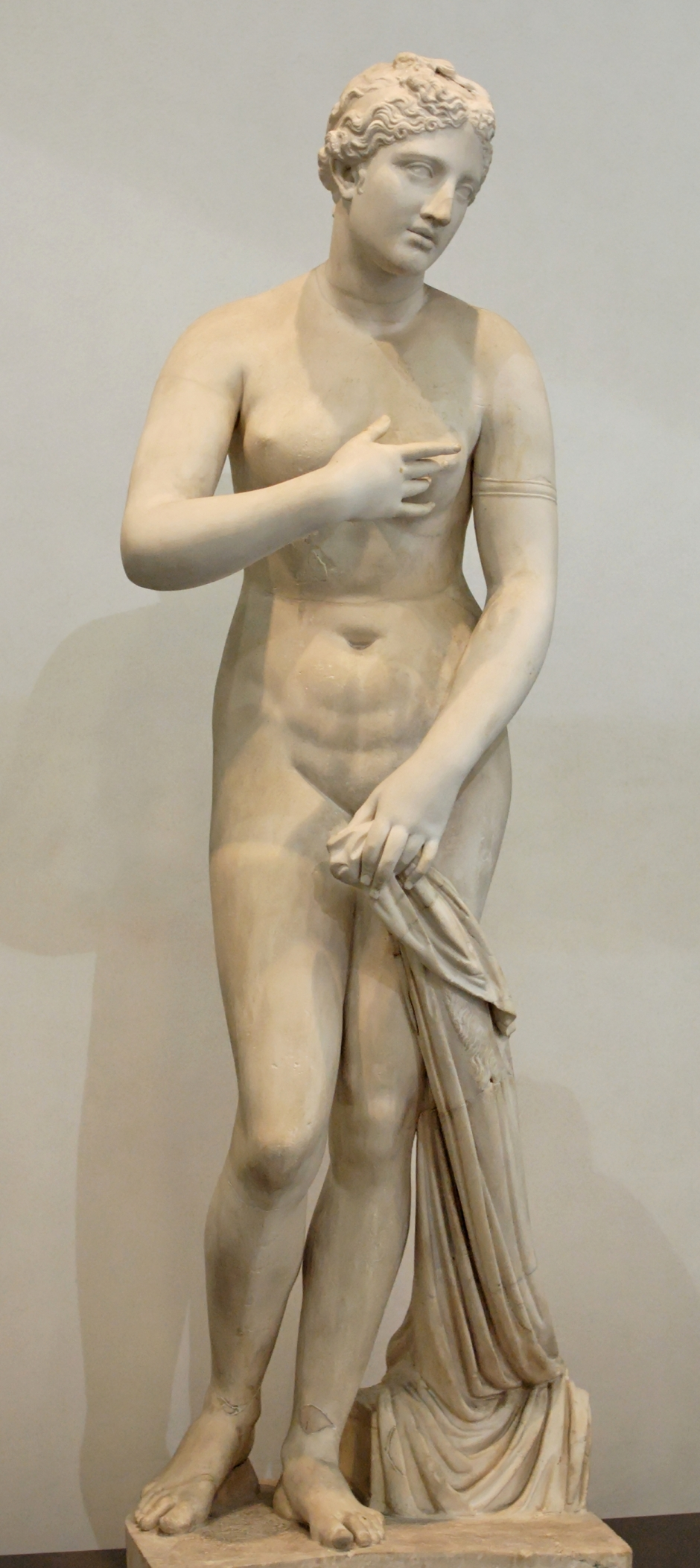 The Aphrodite of Menophantos, dating from 1C BC is one of many variants of a sculptural pose called the Venus Pudica (modest Venus). It derives from a sculpture by Praxiteles but has been adjusted in two key ways. Firstly, Venus is adopting an aware and self-conscious pose and, secondly, the position of her arms has been adjusted to protect her modesty. That intrinsic modesty has made this one of the most enduring forms of female nude.