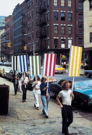 "Daniel Buren, Seven Balets in Manhatten (1975) ""Every act is political and, whether one is conscious of it or not, the presentation of one's work is no exception. Any production, any work of art is social, has a political significance"" Dancers carrying placards of Buren's striped paintings seek to reclaim the social ambitions of Geometric Abstraction, taking it into the streets. The strip was defined as form of resistance, and they were also pasted on top of advertising posters to 'silence the siren calls of capitalism'."