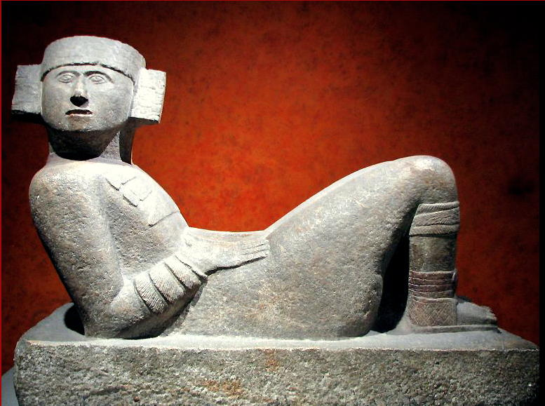 "A pre-Columbian Chac Mool figure from what is now Mexico. Henry Moore saw pictures of these figures early in his career and they profoundly influenced the development of his work, both intellectually and practically. As he said: ""There are three fundamental poses of the human figure. One is standing, the other is seated, and the third is lying down. Now if you like to carve the human figure in stanone, as I do, the standing pose is no good ... the figure will break off at the ankles ... the early Greeks solved this problem by draping the figure and covering the ankles .... but with either the seated or the reclining figure one does't have this worry""."